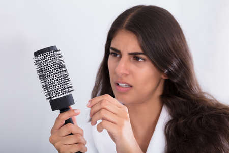 loose hair: Young Woman In Bathrobe Holding Comb Looking At Hair Loss At Home