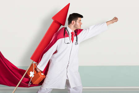Young Superhero Doctor Carrying First Aid Box While Flying On Rocket