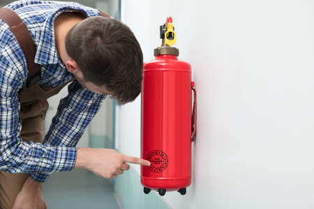 Close-up Of Technicians Hand Pointing To Symbol On Red Fire Extinguisher Against White Background