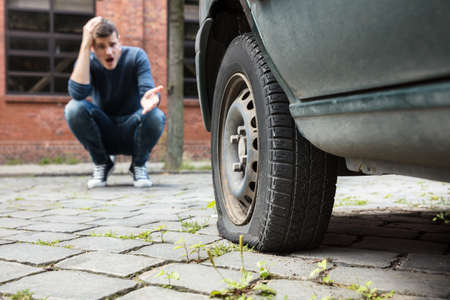 Crouched Worried Young Man With Hand On Head Pointing At Punctured Car Tire