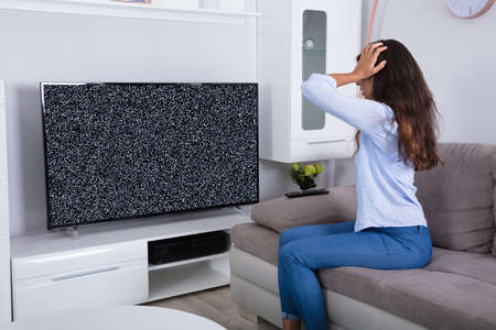 Rear View Of A Woman On Sofa Getting Frustrated With Glitch TV Screen At Home
