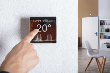 Finger Touching Digital Thermostat Temperature Controller At Home
