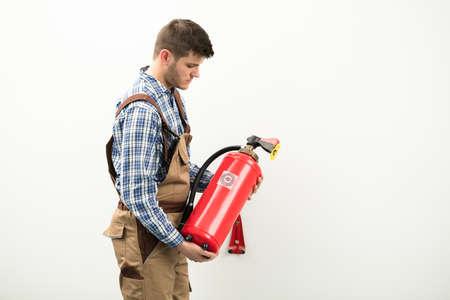 Técnico joven que lleva el extintor rojo contra el fondo blanco Foto de archivo - 88555363