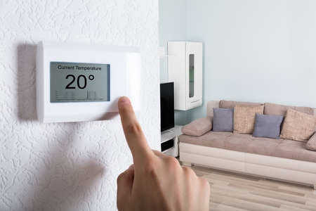 Close-up Of A Person's Hand Adjusting Digital Thermostat At Home Stockfoto