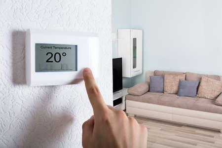 Zbliżenie dłoni osoby regulacji termostatu cyfrowego w domu Zdjęcie Seryjne