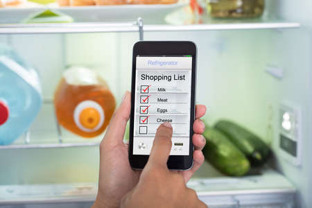 Close-up Of Person Hands Marking Shopping List On Mobile Phone In Front Open Fridge