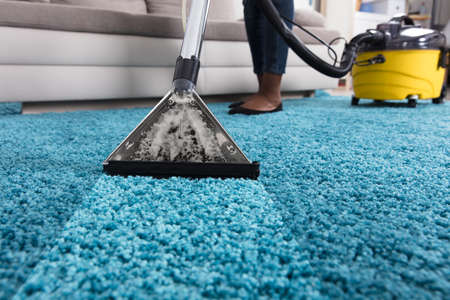 Person Using Vacuum Cleaner For Cleaning Blue Carpet At Home Banque d'images