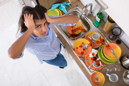 Frustrated Young Woman Standing Near Messy Utensils On Countertop In Kitchen Stock Photo