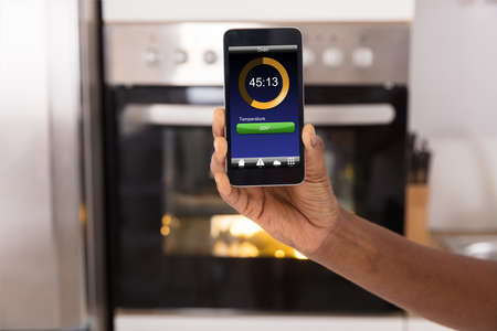 Close-up Of Woman Operating Oven Appliance With Mobile Phone App