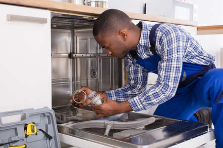 Jonge Afrikaanse hersteller die afwasmachine in keuken herstellen