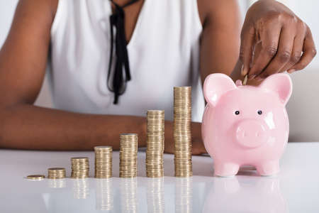 Human Hand Putting Coin In Piggybank Besides Stacked Coins Stock Photo