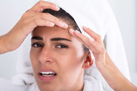 tensed: Close-up Of Young Woman Looking At Pimple And Squeezing On Forehead