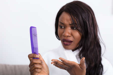 Woman Holding Comb Looking At Loss Hair Banco de Imagens