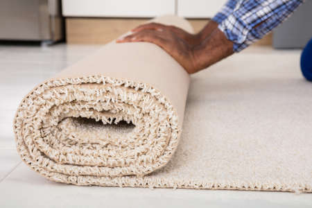 Close-up Of Workers Hands Rolling Carpet At Home