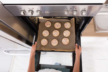 High Angle View Of A Human Hand Baking Cookies In Microwave Oven Lizenzfreie Bilder