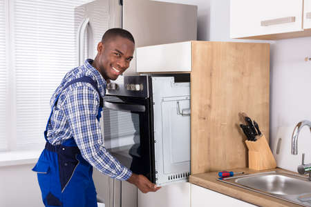 Male African Technician In Overall Installing Oven In Kitchen Reklamní fotografie