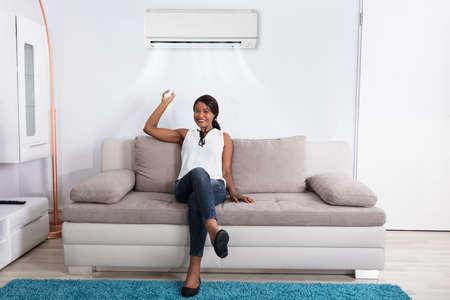 Gelukkige Afrikaanse vrouwenzitting op bank die airconditioner thuis met behulp van Stockfoto