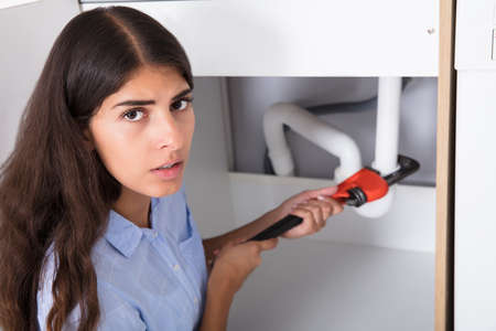 Close-up Of Young Woman Tightening Sink Pipe With Monkey Wrench In Kitchen
