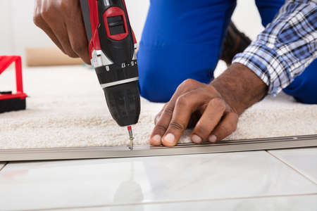 Person Hand Installing Carpet On Floor Using Wireless Screwdriver