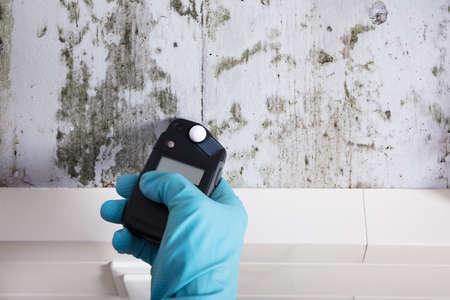 Close-up van persoon Hand dragen handschoenen meten van de vochtigheid van een beschimmelde muur Stockfoto