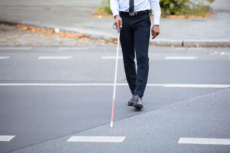 Blind Person With White Stick Walking On Street Stock Photo