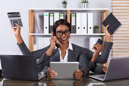 Fatigué jeune femme africaine multitâche travailler sur ordinateur portable au bureau