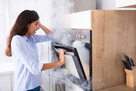 Shocked Young Woman Looking At Smoke Coming From Oven In Kitchen Stockfoto