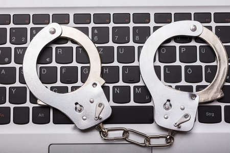 High Angle View Of Handcuffs On Laptop Keyboard