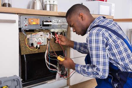 Młody mężczyzna afrykański technik mocowanie zmywarki z multimetrem cyfrowym w kuchni