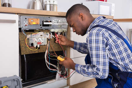 Young Male African Technician Fixing Dishwasher With Digital Multimeter In Kitchen Imagens - 92338601