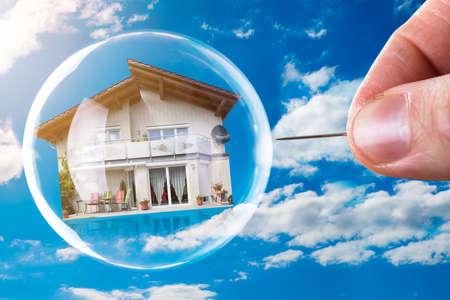 Menschliche Hand, die Haus und Blase mit Nadel gegen bewölkten Himmel stößt