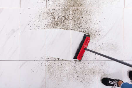 High Angle View Of Broom Cleaning Dirt On Tiled Floor At Home