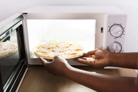 Close-up Of A Young African Woman Baking Pizza In Microwave Oven Lizenzfreie Bilder