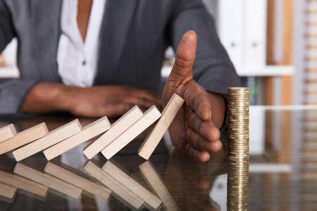Zbliżenie ludzkiej dłoni, zatrzymując drewniane klocki przed upadkiem na ułożonych monet na biurku