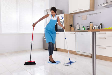Housewife Doing Multitasking Household Work By Sweeping And Mopping In Kitchen