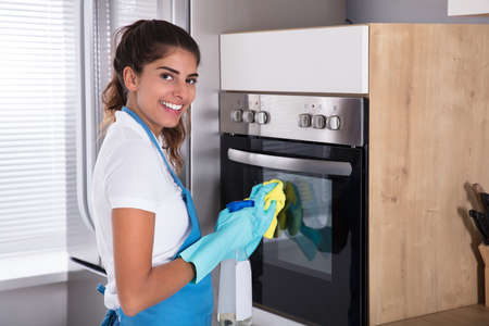 Beautiful Woman In Protective Gloves Cleaning Oven With Spray Bottle And Rag Фото со стока
