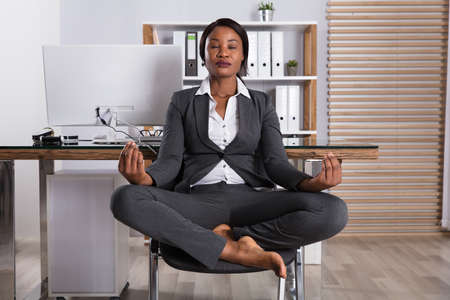 African Woman Meditating On Chair With Eyes Closed At Workplace