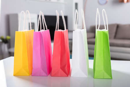 Close-up Of Multi Colored Shopping Bags On White Desk