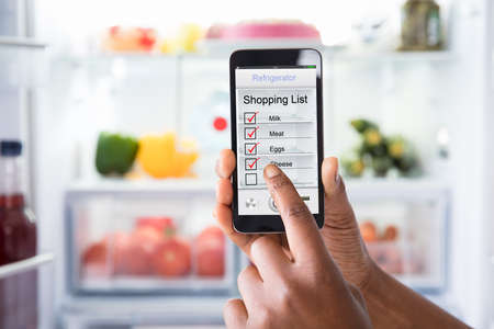 Close-up Of Human Hand Marking Shopping List On Mobile Phone In Front Open Fridge