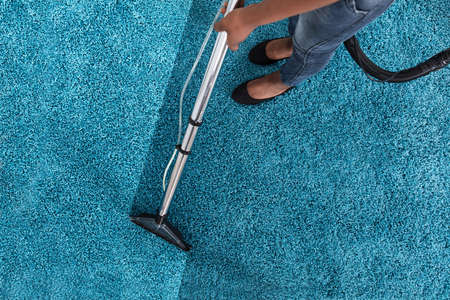 Person Using Vacuum Cleaner For Cleaning Blue Carpet At Home Lizenzfreie Bilder