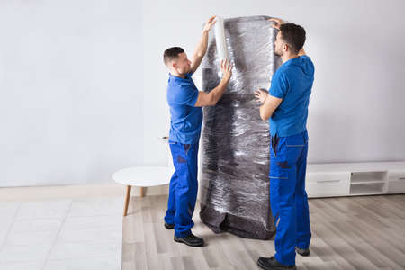 Two Young Male Movers Packing Furniture In Living Room