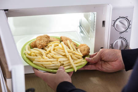 Close-up Of A Persons Hand Putting Fried Food Inside Microwave Oven