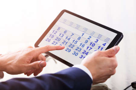 Close-up Of A Businesspersons Hand Using Calendar On Digital Tablet