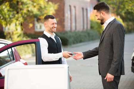 Smiling Young Businessman Standing Beside Car Getting Key From Valet