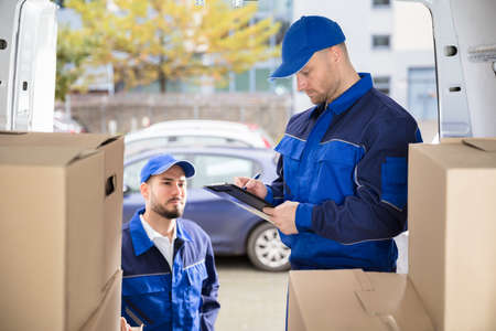 Young Male Mover Looking At His Partner Writing On Clipboard Near Cardboard Boxes