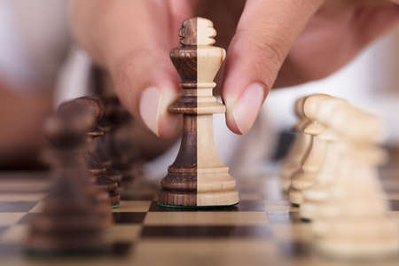 Close-up Of Person Hand Playing Chess And Holding King Chess Piece On Board Stock Photo