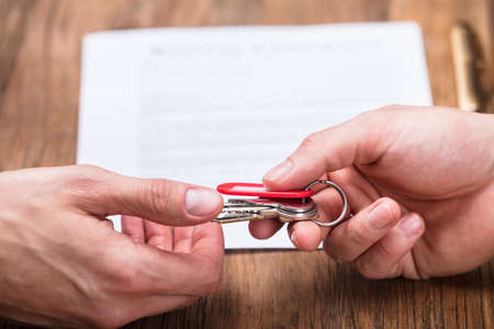 Close-up Of Real Estate Agent Giving House Key To Owner With Contract Form On Table