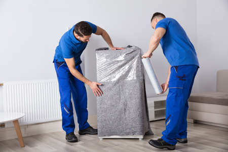 リビングルームに家具を梱包する2人の若い男性の引っ越し 写真素材
