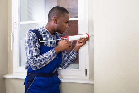 Close-up Of A Young Male Worker Applying Silicone Sealant With Silicone Gun Stock Photo