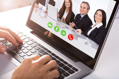 Close-up Of A Businessperson's Hand Video Conferencing With Male And Female Colleague On Laptop